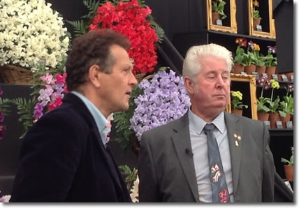 Monty Don from the BBC interviews Derek Heathcote in front of the                        Eagle Sweet Peas stand at the Chelsea Flower Show in 2015